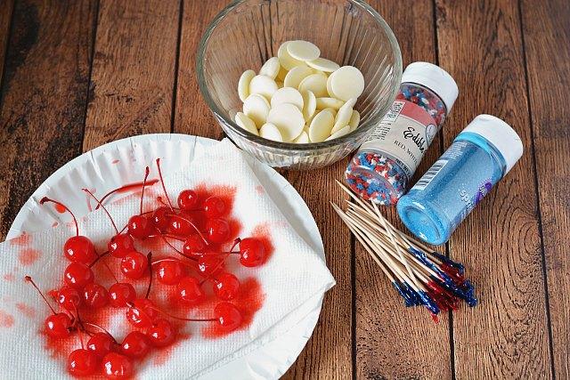 Maraschino cherries, white chocolate wafers, sprinkles, and toothpicks