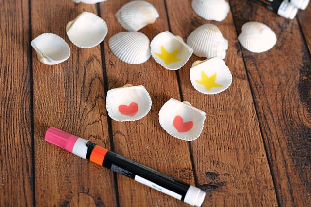 Seashells with hearts and stars drawn on the inside with a paint pen laying nearby