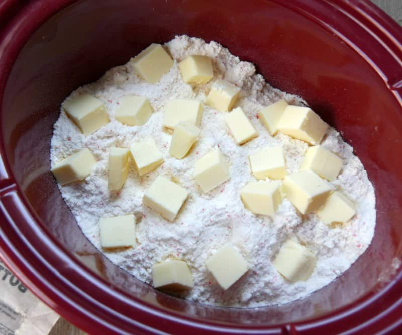 Cubed butter on top of cake mix in a red oval slow cooker