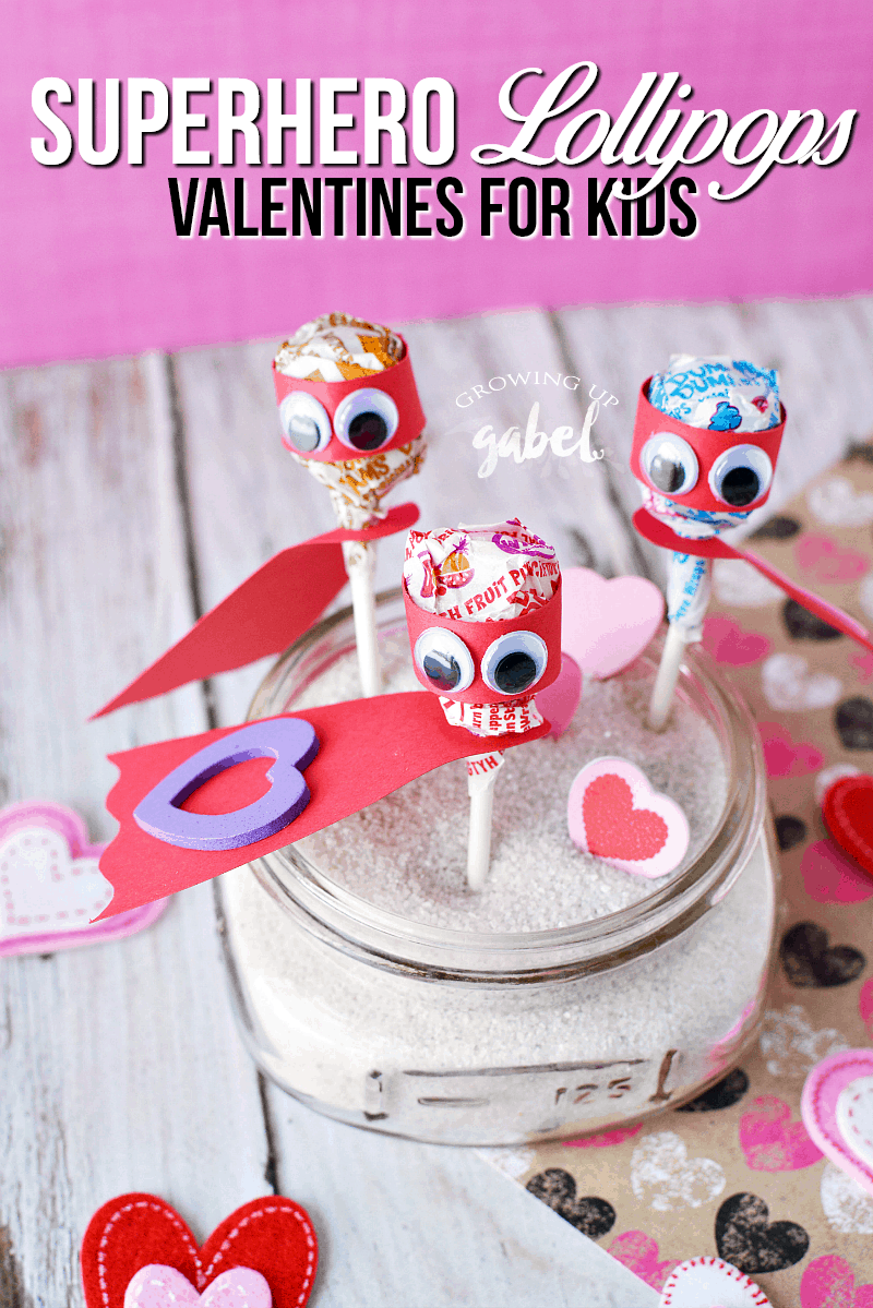 Lollipop superhero valentines day cards are made out of Dum Dum lollipops, construction paper, and googly eyes! Perfect for Valentines Day parties for kids!
