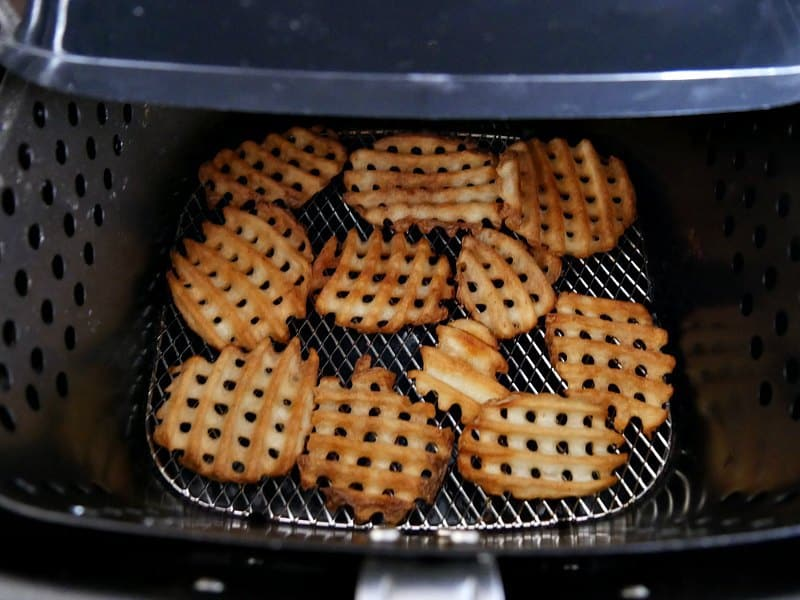 Waffle fries being cooked in an air fryer to be used as the base layer for Irish nachos recipe.