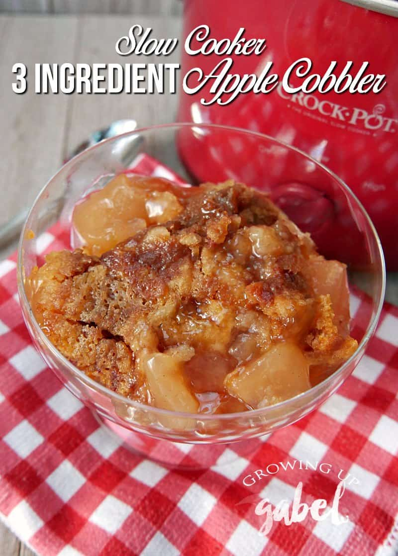 A serving of apple cobbler with a red Crock Pot behind it and a checkered towel underneath.