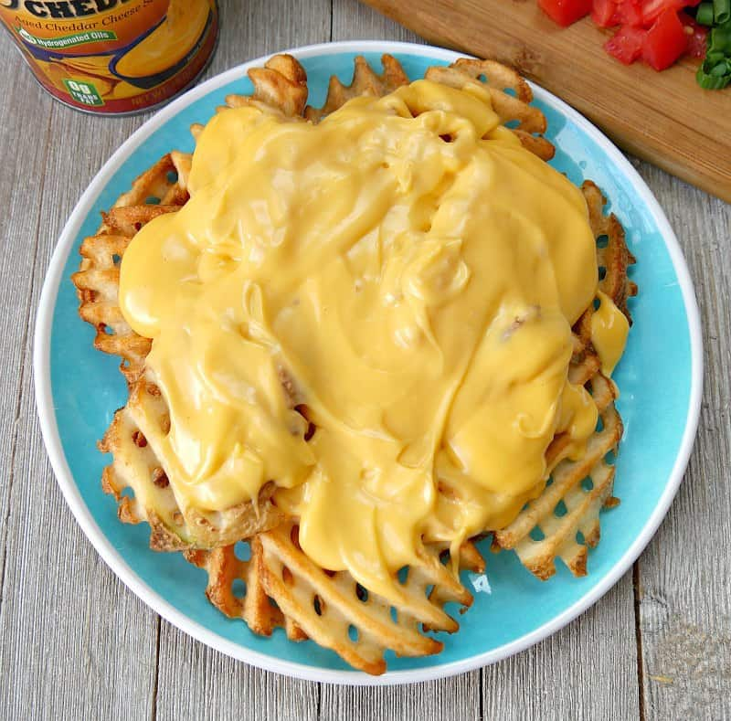 Plate of waffle fries topped with Ricos nacho cheese to make Irish nachos.