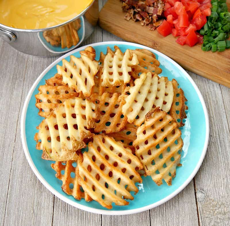 Plate of cooked waffles fries to make Irish nachos.