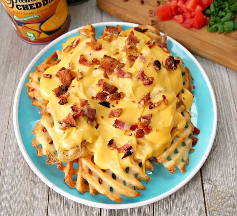 plate of waffles fries topped with nacho cheese and cooked diced bacon being used to make Irish nachos