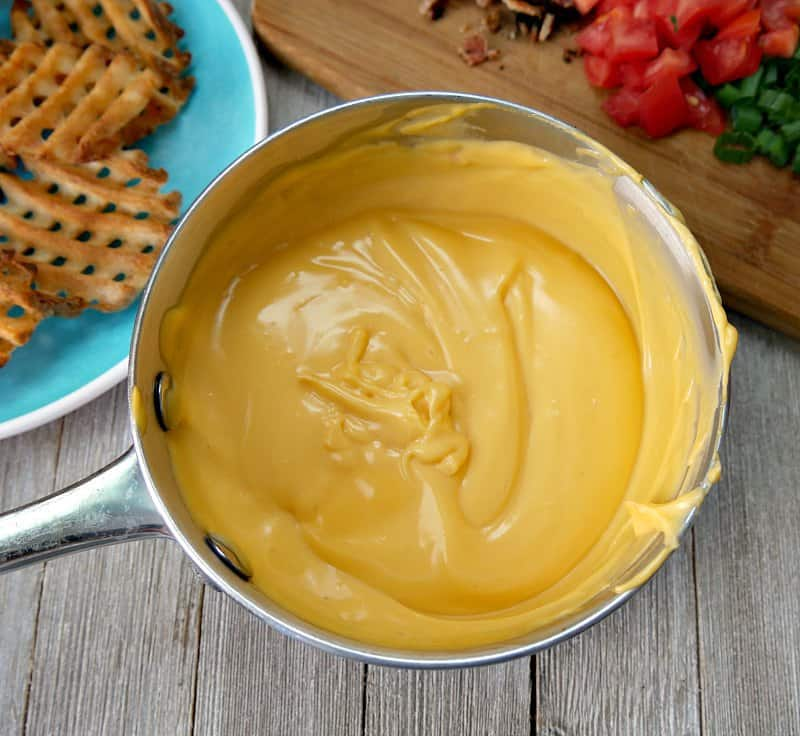 A small pot full of warmed up Ricos nacho cheese as a topping for Irish nachos.