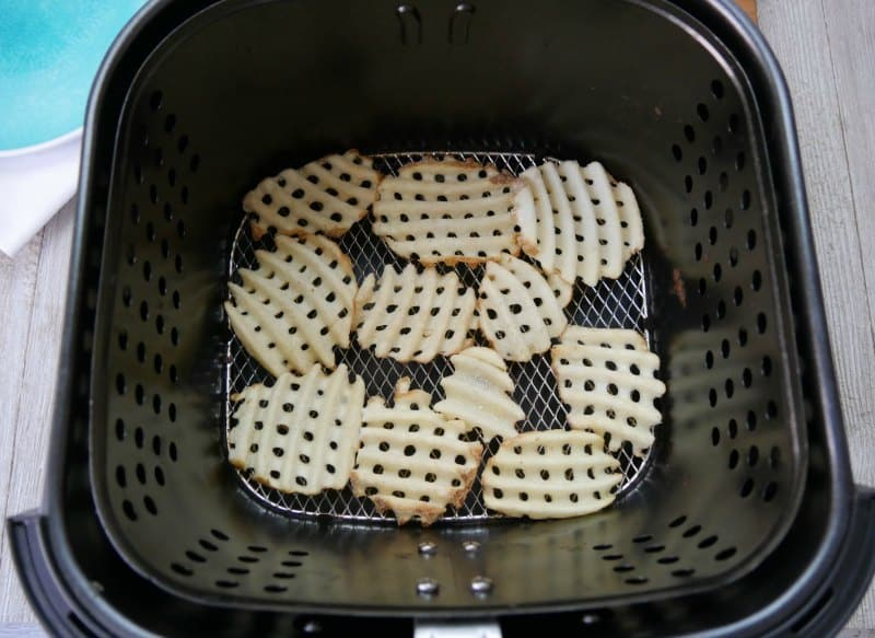 Frozen waffle fries being cooked in an air fryer in order to make Irish nachos.