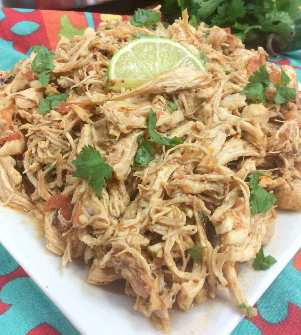shredded chicken on a plate with a slice of lime on top