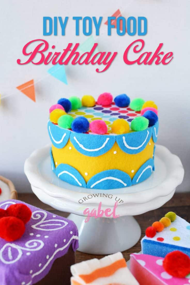 Use felt, pom poms and puffy paint along with an old tin to create a colorful toy food birthday cake.