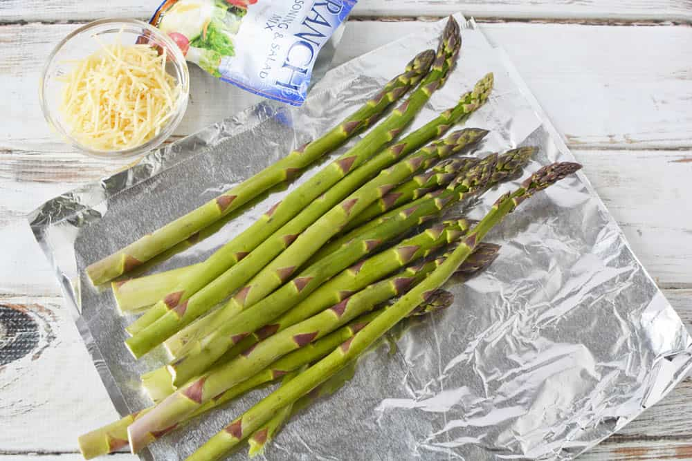 Fresh asparagus on a piece of foil with a ranch dressing packet mix and small bowl of Parmesan cheese.
