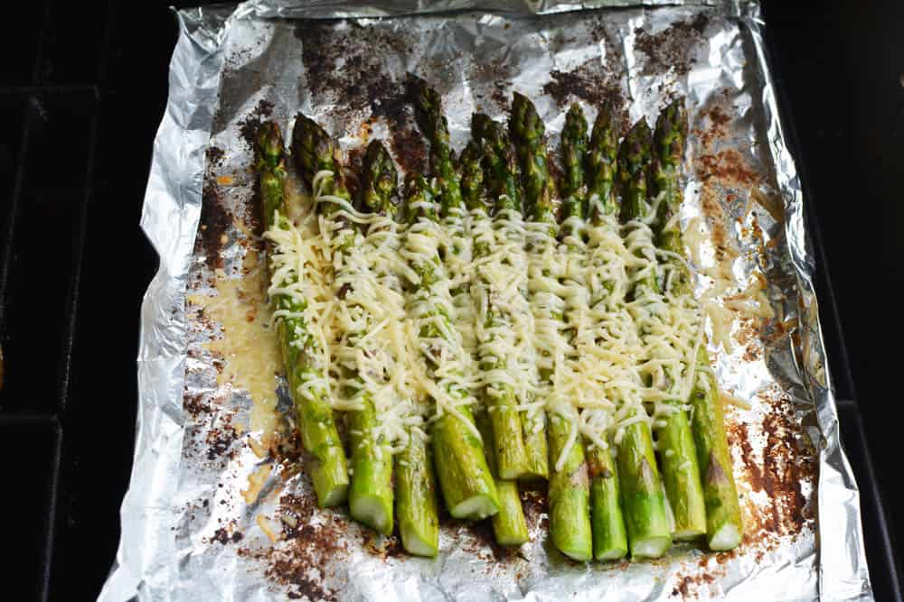 Grilled asparagus on grill covered in melted cheese
