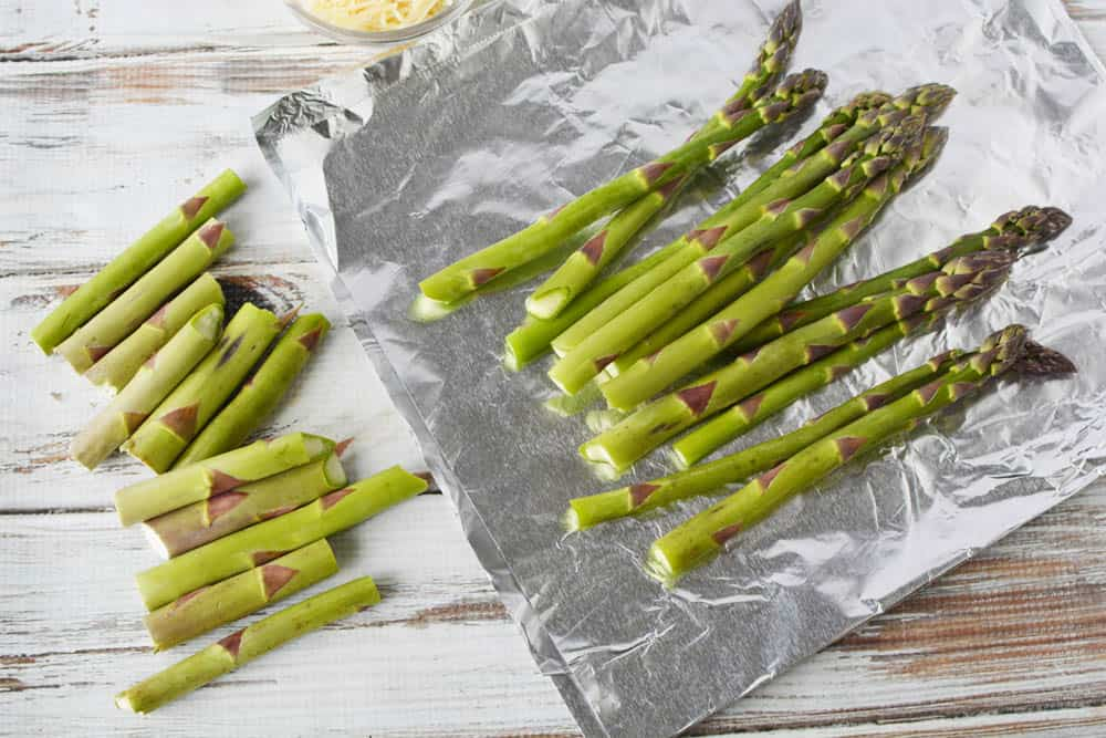 Fresh asparagus on piece of foil with ends trimmed off.