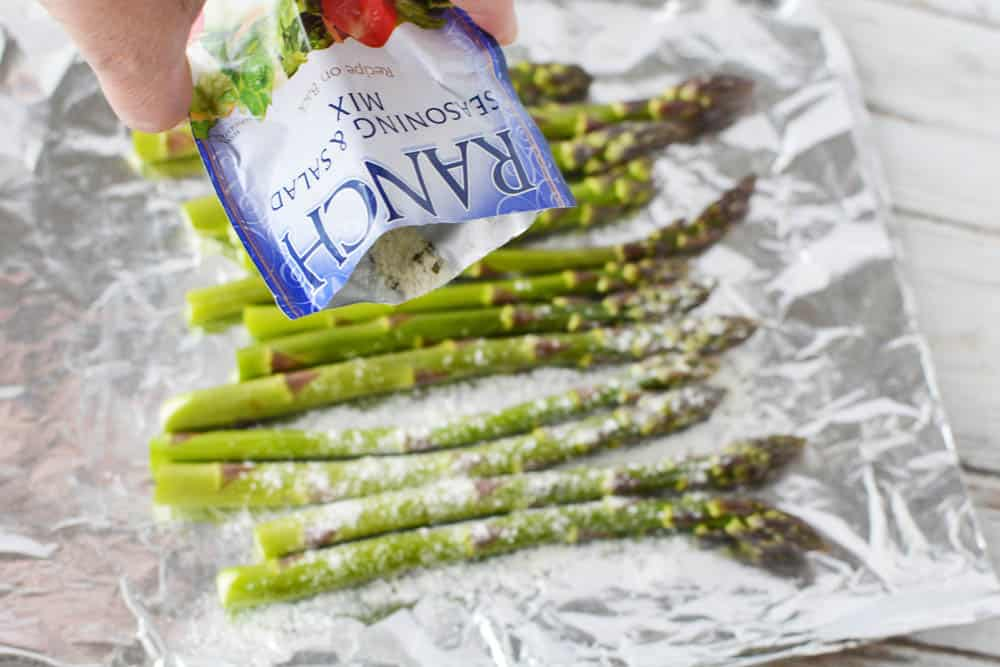 A packet of ranch dressing mix being poured over asparagus on foil
