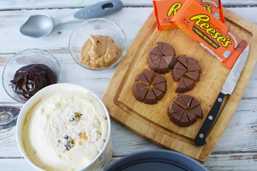 A tub of ice cream with bowls of fudge and peanut butter next to a cutting board with cut up Reese's Peanut Butter cups.