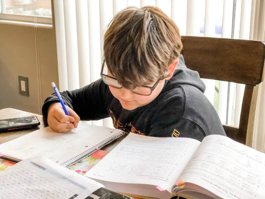 young boy doing homework at kitchen table