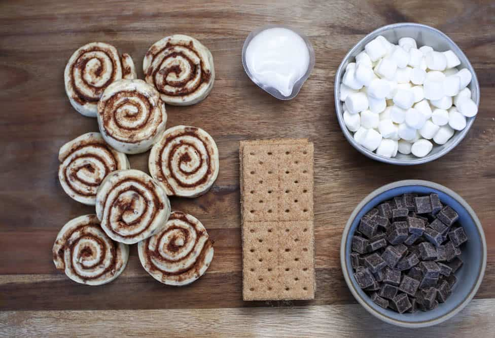 Ingredients to make s'mores monkey bread: cinnamon rolls, graham crackers, frosting, marshmallow and chocolate chunks