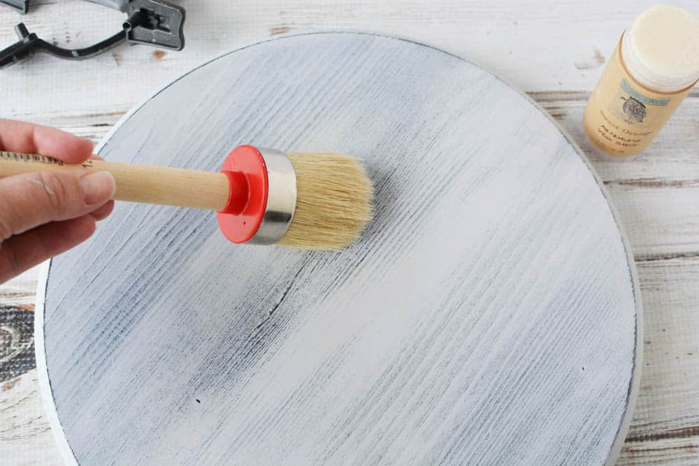 chalk paint wax being put on a painted and distressed wood circle