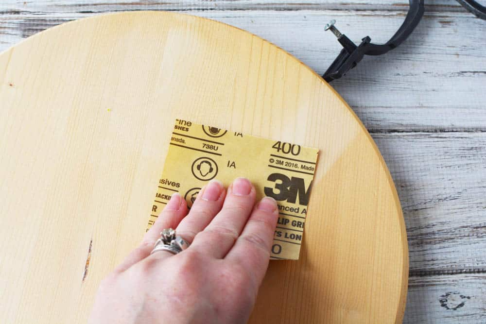 a hand sanding a wood circle with sand paper