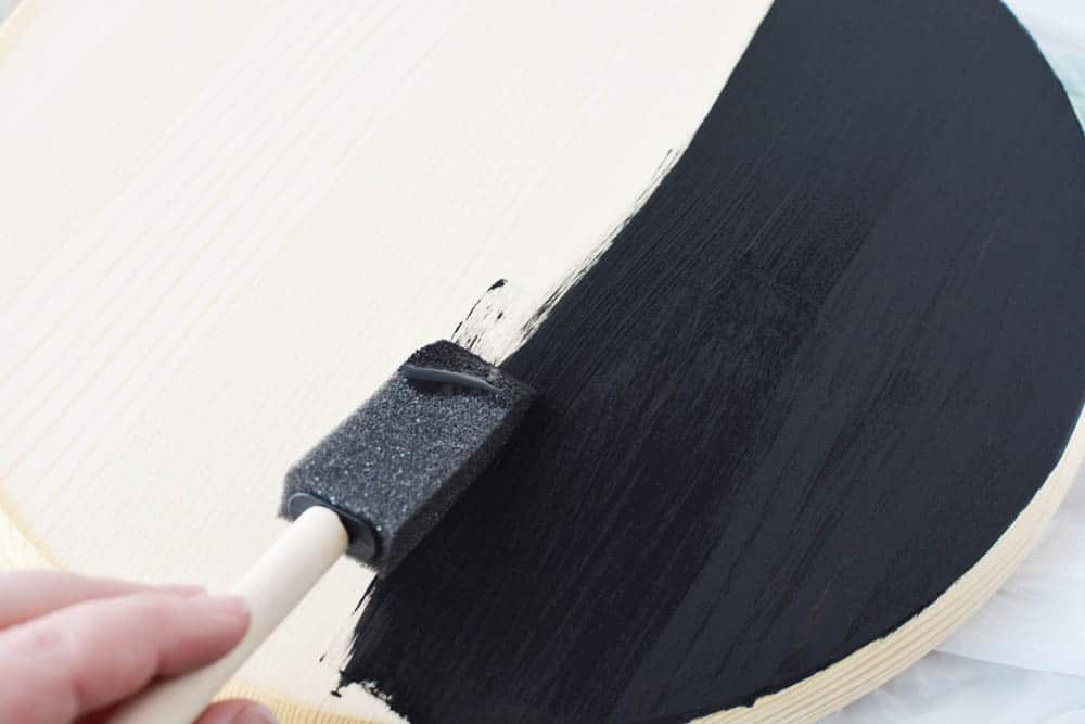 someone painting a wood circle black with a sponge brush