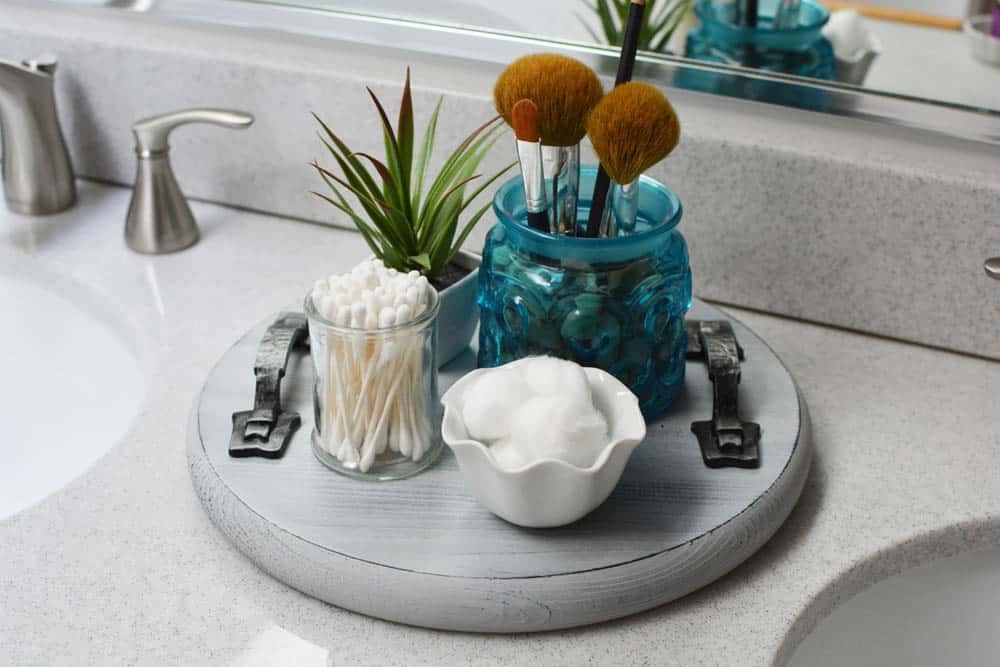 Round wood tray on bathroom counter with brushes, cotton balls, cotton swabs and a plant