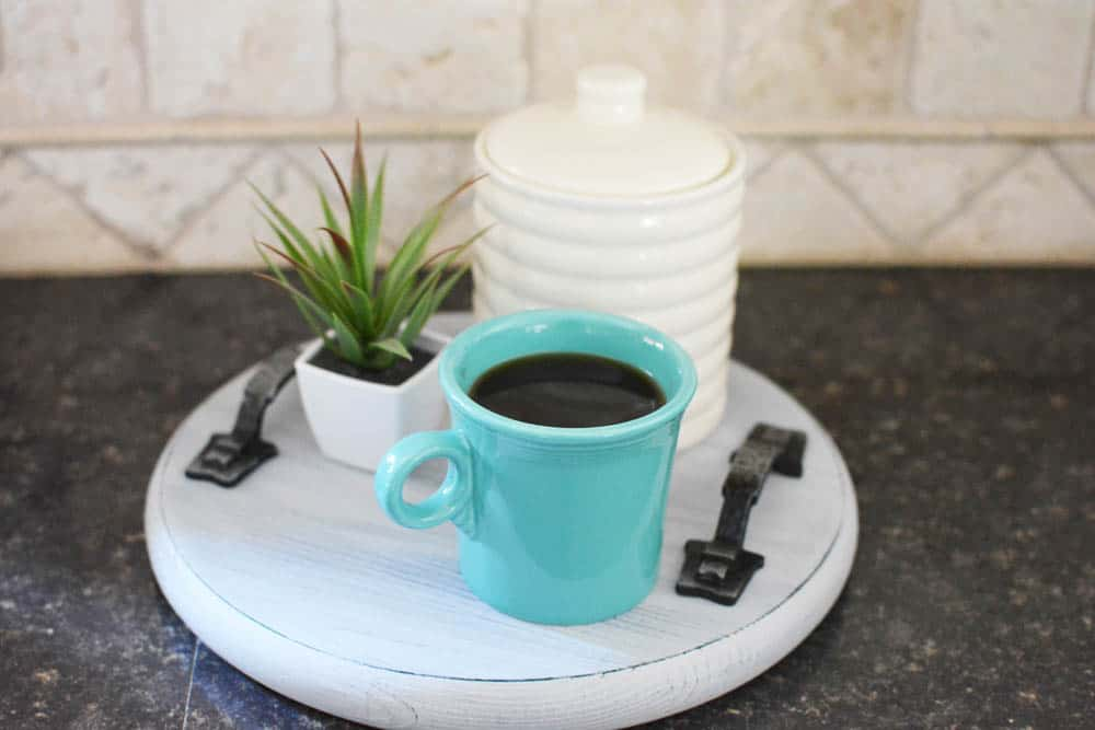 Turquoise coffee mug filled with coffee on a tray with a plant and white canister on counter