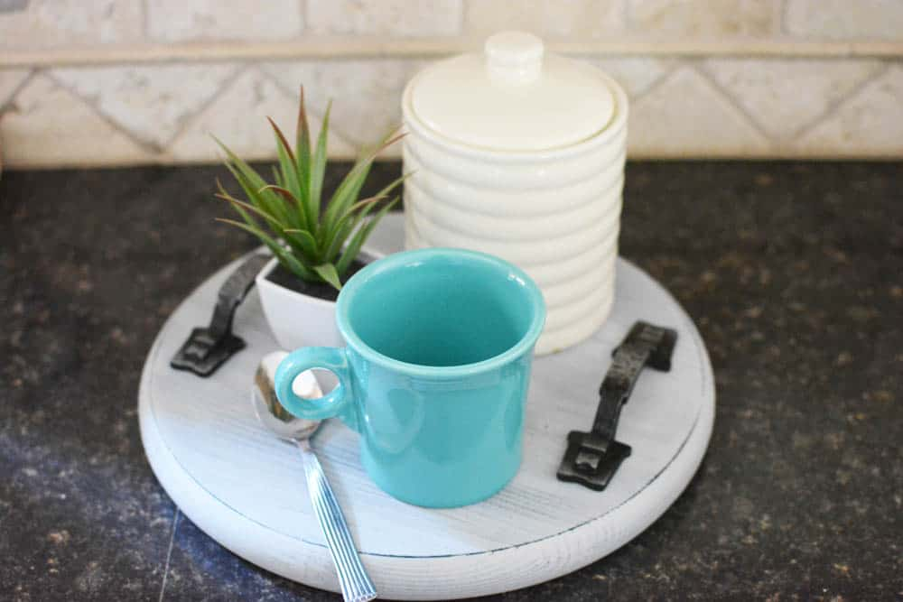 turquoise cup sitting on top of a wood tray along with a small plant and a whit cansiter