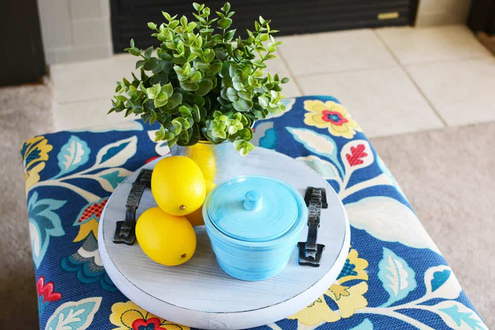 wood tray on a floral ottoman with lemons, plant and turquoise canister on it