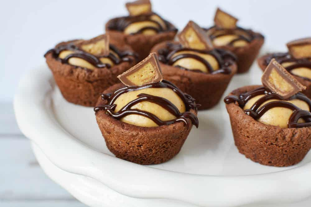 chocolate peanut butter cookie cups with candy on top on white platter